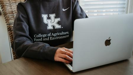 student working on laptop in college sweatshirt