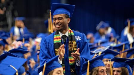 Student standing and smiling, clapping at graduation ceremony