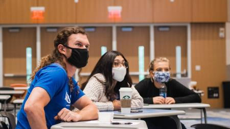 students in masks listening to lecture